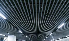 Lights and ventilation system in long line on ceiling of the dark office industrial building exhibition Hall Ceiling construction. Lights and ventilation system Stock Images