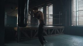 Lightweight boxer punching bag in the gym slowmotion. Lightweight boxer training in the dark vintage stylized gym. Caucasian young man with boxing gloves hitting stock video footage