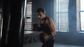 Light weight boxer training in vintage stylized gym. Lightweight boxer training in dark vintage stylized gym. Caucasian young man with boxing gloves hitting the stock video