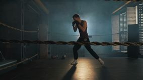 Lightweight boxer training on the ring in vintage stylized gym. Lightweight boxer training in stylized gym. Caucasian young man fight the shadow on the old stock footage