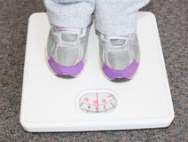 Lightweight Child on Bathroom Scales. Stock Photo