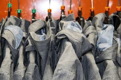 Lightweight grey raincoats on a rack against an orange background. Several identical Lightweight grey raincoats on a rack against an orange background royalty free stock photo