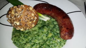 Lightweight specialty. 'Kranjska' sausage with spinach and spring onions Royalty Free Stock Photography