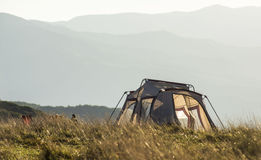 Lightweight tent and hiker on a mountain top. Stock Image