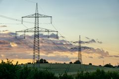 Ligne électrique à haute tension avec le pylône à un champ agricole Photos stock