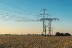 Ligne électrique à haute tension avec le pylône à un champ agricole Image libre de droits