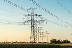 Ligne électrique à haute tension avec le pylône à un champ agricole Images libres de droits