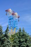 Ligne électrique à haute tension - bleu Grande taille au-dessus des arbres Ciel de ressort Photos libres de droits