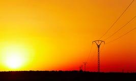Ligne électrique électrique contre le ciel coloré au coucher du soleil Images stock