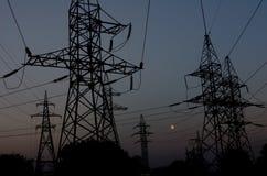 Ligne électrique de confiance contre le ciel nocturne Images stock
