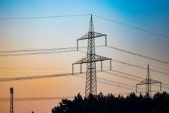 Ligne électrique de pylône et de boîte de vitesses dans le coucher du soleil photos libres de droits