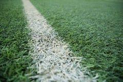 Ligne blanche de rayure sur le lancement vert du football image stock