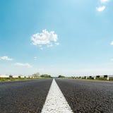 Ligne blanche sur la route goudronnée et le ciel avec des nuages Photographie stock