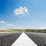ligne blanche sur le plan rapproché de route goudronnée et le ciel bleu Photographie stock libre de droits
