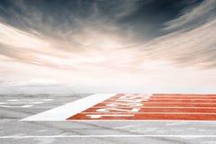 Ligne d'arrivée vide de voie contre le ciel nuageux dramatique Image libre de droits