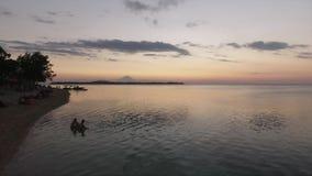 Ligne de côte, mer avec de l'eau toujours reflétant le ciel clair au coucher du soleil dans l'heure d'été banque de vidéos