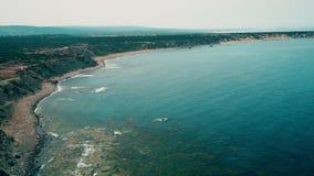 Ligne de côte de vue de bourdon longue sur la plage sauvage de mer Éclaboussure d'eau de mer sur la côte rocheuse clips vidéos