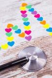 Ligne de cardiogramme des coeurs et du stéthoscope de papier sur le concept en bois de fond, de médecine et de soins de santé Image stock