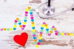 Ligne de cardiogramme des coeurs et du stéthoscope de papier sur le concept en bois de fond, de médecine et de soins de santé Photographie stock libre de droits