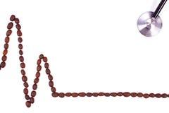Ligne de cardiogramme des graines de café et du concept de stéthoscope, de médecine et de soins de santé Images stock