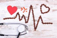 Ligne de cardiogramme des graines de café, les pilules de stéthoscope et de supplément, la médecine et le concept de soins de san Photos stock