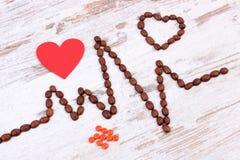 Ligne de cardiogramme des graines de café, les pilules rouges de coeur et de supplément, la médecine et le concept de soins de sa Photos stock
