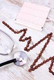 Ligne de cardiogramme des graines de café rôties et du concept de stéthoscope, de médecine et de soins de santé Photo libre de droits