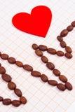 Ligne de cardiogramme des graines de café rôties et du concept rouge de coeur, de médecine et de soins de santé Photos stock
