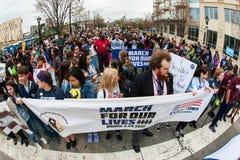 Ligne de milliers derrière la bannière chez mars pendant nos vies Photos stock