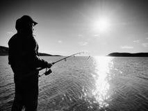 Ligne de pêche de contrôle de pêcheur et poussée de l'amorce sur la tige Silhouette de pêcheur au coucher du soleil Photographie stock