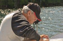 Ligne de pêche de fixation d'homme supérieur photographie stock libre de droits