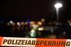 Ligne de police devant des lumières de ville par nuit Photographie stock