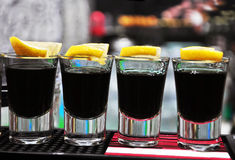 Ligne de quatre boissons de vodka noire sur le bar Images stock