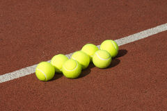 Ligne de sept billes de tennis jaunes sur la cour Photos stock