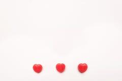 Ligne de sucrerie de forme de coeur de jour du ` s de Valentine de trois rouges sur le fond de livre blanc Concept d'amour Style  Photographie stock