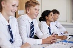 Ligne des étudiants de lycée portant la séance uniforme au bureau dans la salle de classe image libre de droits