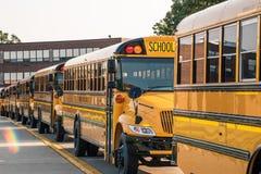 Ligne des autobus jaunes le long du trottoir devant l'école image libre de droits