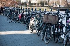 Ligne des bicyclettes contre une frontière de sécurité à un canal Images stock