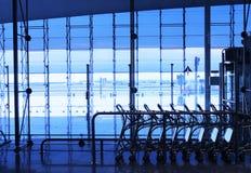 Ligne des chariots de bagage à l'aéroport occupé Photographie stock