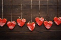 Ligne des coeurs rouges de pains d'épice sur le ruban Photos stock