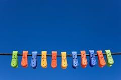 Ligne des pinces à linge en plastique multicolores Images libres de droits