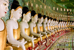 Ligne des statues de Bouddha avec la robe longue d'or Photographie stock libre de droits