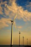 Ligne des turbines de vent au coucher du soleil Photos libres de droits