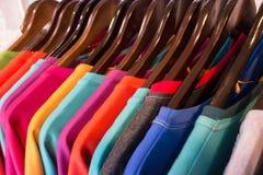 Ligne des vêtements colorés multi sur les cintres en bois dans le magasin Vente Photo stock