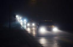 Ligne des voitures en brouillard, avec les phares brillants dans une nuit brumeuse Photos libres de droits