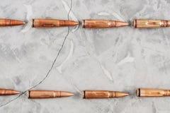 Ligne deux des balles en métal pour le fusil d'assaut sur le béton cassé gris photo libre de droits