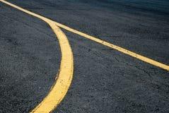 Ligne deux jaune fusionnant dans la piste ou la rue La ligne jaune de deux rues deviennent une Images stock