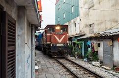 Ligne ferroviaire passant entre les bâtiments étroits dans le vieux quart de Hanoï Image libre de droits