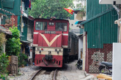 Ligne ferroviaire passant entre les bâtiments étroits dans le vieux quart de Hanoï Photographie stock libre de droits