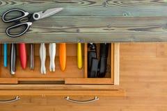 Ligne ordonnée des couteaux colorés dans un tiroir adapté photo stock